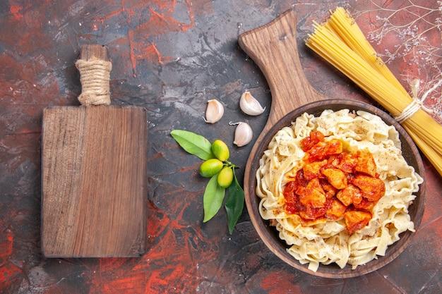Bovenaanzicht kip met deeg pastagerecht op donkere vloer schotel donker pastadeeg
