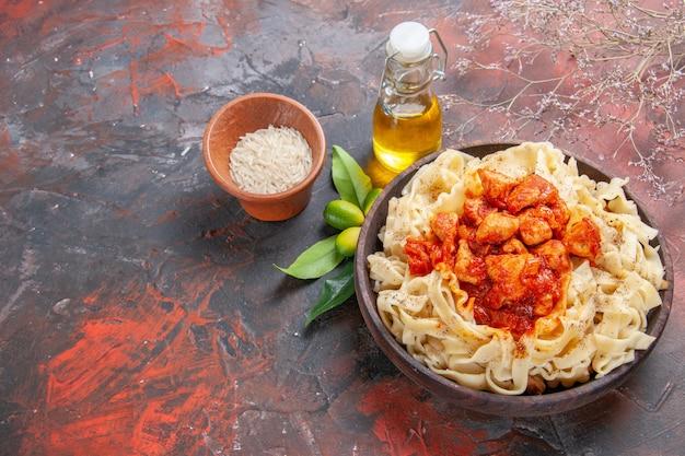 Bovenaanzicht kip met deeg pastagerecht op het deeg van de donkere oppervlakte van de deegwarenmaaltijd