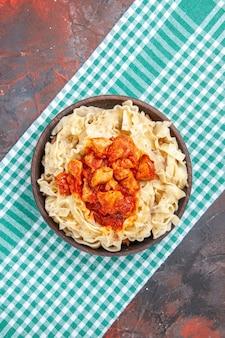 Bovenaanzicht kip met deegpastaschotel op de donkere kleur van de de pastaschotel van de oppervlaktemaaltijd