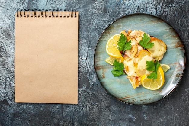 Bovenaanzicht kip met kaas op plaat notebook op grijze tafel