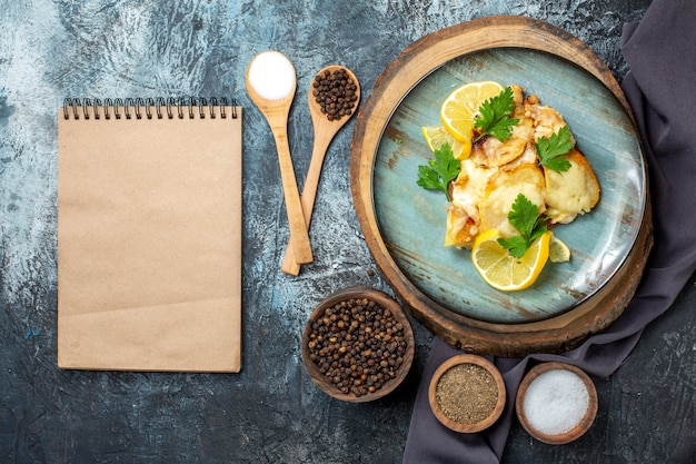 Bovenaanzicht kip met kaas op plaat op houten bord kruiden in houten lepels kladblok op grijze tafel