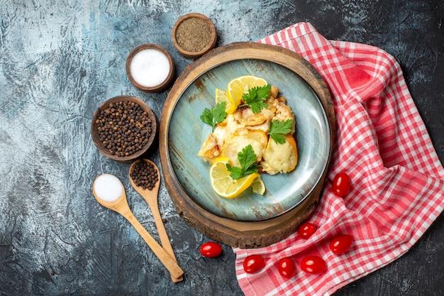 Bovenaanzicht kip met kaas op plaat op houten bord kruiden in kommen op grijze tafel