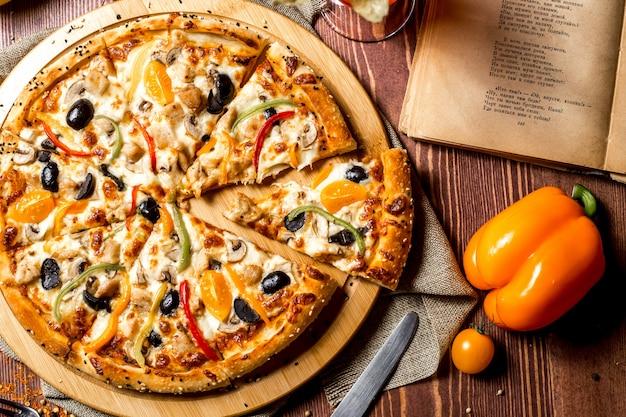 Bovenaanzicht kip pizza met gele kerstomaatjes en paprika op het bord