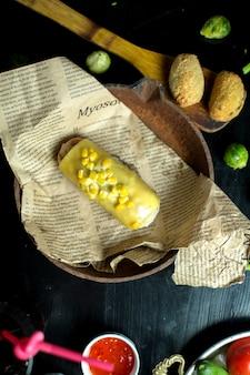 Bovenaanzicht kip schnitzels met maïs en roomkaas op krant in een pan