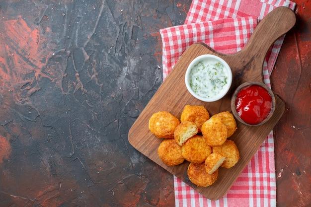 Bovenaanzicht kipnuggets en sauzen op snijplank op donkerrode muur met vrije ruimte