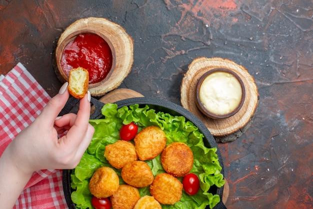 Bovenaanzicht kipnuggets en sauzen op snijplanknugget in vrouwelijke hand op donkerrode muur