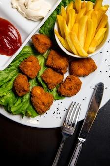Bovenaanzicht kipnuggets met frietjes ketchup en mayonaise