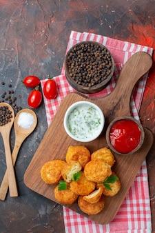 Bovenaanzicht kipnuggets op houten bord met sauzen zwarte peper en zout in houten lepels cherrytomaatjes op donkere tafel