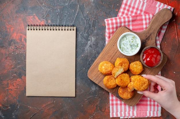 Bovenaanzicht kipnuggets op snijplank met sauzen nugget in vrouwelijke hand rood wit geruit keukenhanddoek notitieboekje op donkere tafel