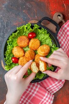 Bovenaanzicht kipnuggets sla cherrytomaatjes in pannugget in vrouwelijke handen op donkere ondergrond