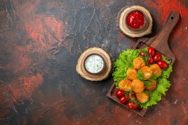 Bovenaanzicht kipnuggets sla cherrytomaatjes op houten bord sauzen in kommen op houten planken op donkere tafel vrije ruimte