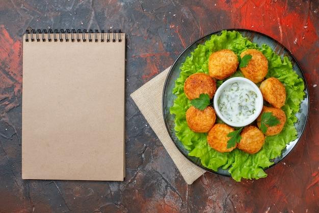 Bovenaanzicht kipnuggets sla en saus op bord spiraal notebook op donkere tafel