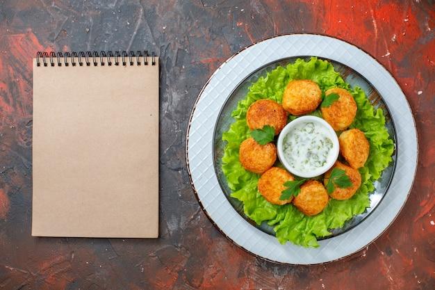 Bovenaanzicht kipnuggets sla en saus op plaat notitieboekje op donkere tafel