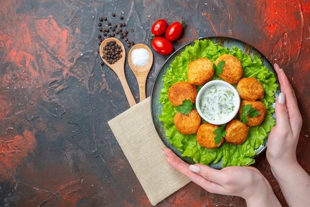 Bovenaanzicht kipnuggets sla op bord in vrouwelijke handen zout en zwarte peper in houten lepels op donkere tafel vrije ruimte