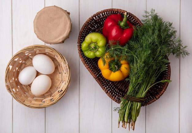 Bovenaanzicht kippeneieren in een mand met yoghurt in een pot met dille en paprika op witte achtergrond