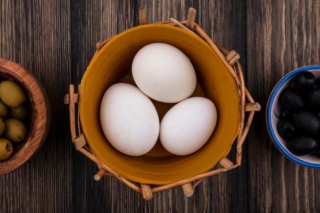 Bovenaanzicht kippeneieren in een mand met zwarte en groene olijven in kommen op houten achtergrond