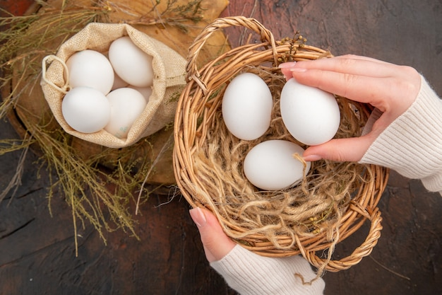 Bovenaanzicht kippeneieren in kleine tas en mand