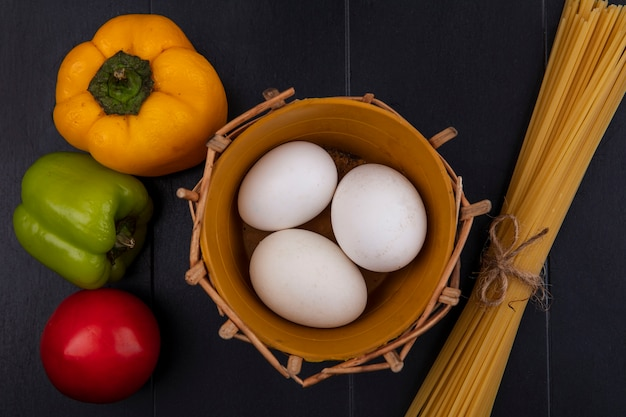 Bovenaanzicht kippeneieren in mand met rauwe spaghetti en paprika op zwarte achtergrond