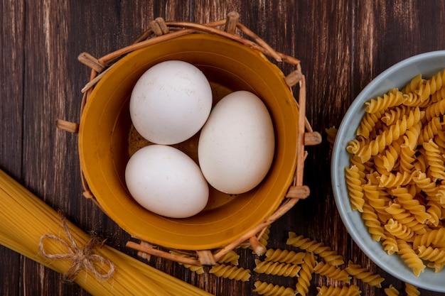 Bovenaanzicht kippeneieren in mand met rauwe spaghetti en pasta op houten achtergrond