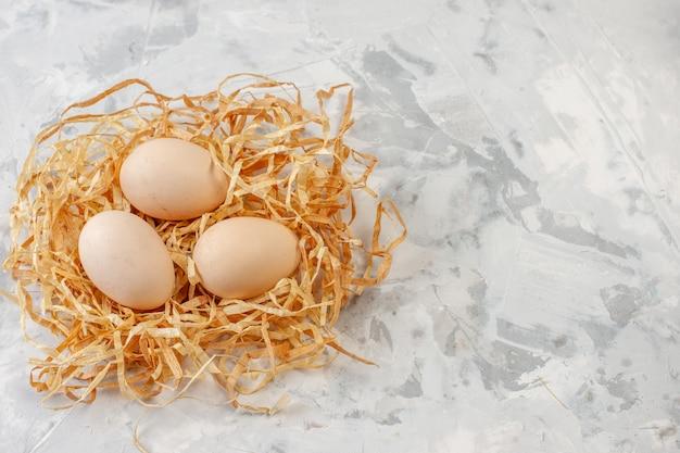 Bovenaanzicht kippeneieren op stro op tafel met kopieerplaats