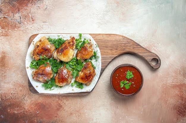 Bovenaanzicht kippenkom saus kip met kruiden op lavash op de snijplank