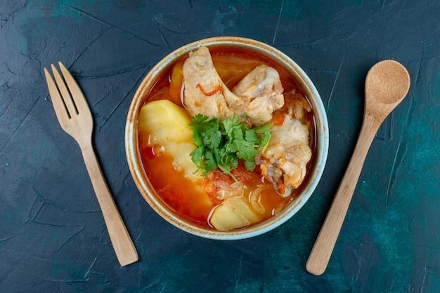 Bovenaanzicht kippensoep met kip en groenten binnen, samen met houten bestek op donkerblauw bureau soep vlees eten diner kip