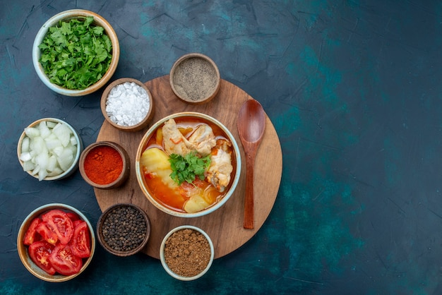 Bovenaanzicht kippensoep samen met kruiden, oliegroenten en verse groenten op het donkerblauwe bureau, soep, vleesmaaltijd