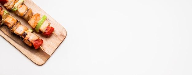 Bovenaanzicht kippenspiesjes op snijplank met kopie-ruimte