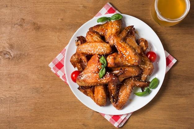 Bovenaanzicht kippenvleugels op plaat met sesamzaadjes en bier