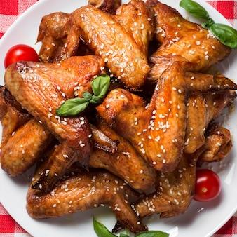 Bovenaanzicht kippenvleugels op plaat met sesamzaadjes en kerstomaatjes