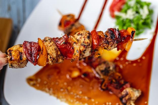 Bovenaanzicht kipspiesjes gegrilde kipfilet met rode en gele pepers kruiden saus en sesamzaadjes op een bord