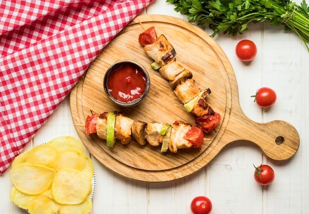 Bovenaanzicht kipspiesjes op snijplank met saus en frietjes