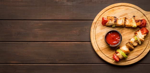 Bovenaanzicht kipspiesjes op snijplank met saus en kopie-ruimte