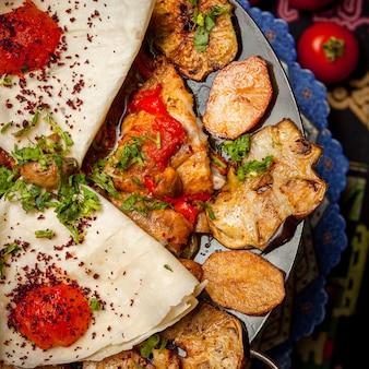 Bovenaanzicht kipzak met gebakken aardappelen en tomaat en lavash
