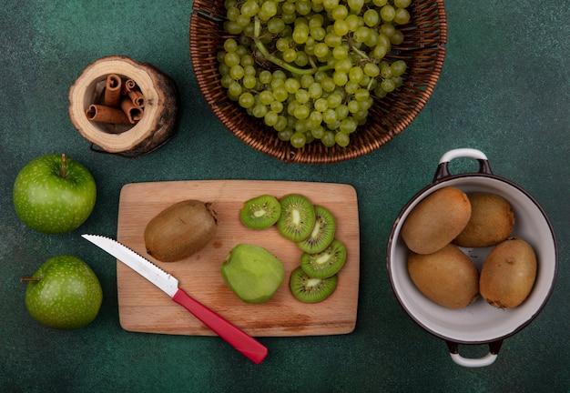 Bovenaanzicht kiwi in een pan met plakjes en een mes op een stand met appels en druiven met kaneel op een groene achtergrond
