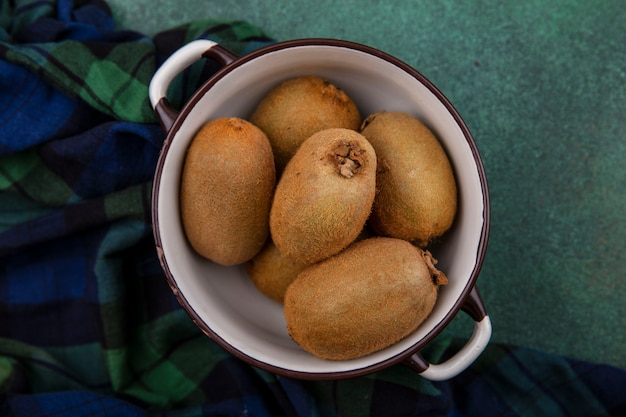 Bovenaanzicht kiwi in een pan op een groen geruite handdoek op een groene achtergrond