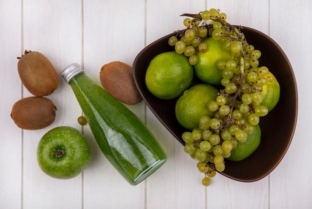 Bovenaanzicht kiwi met fles sap appel en druiven met mandarijnen in kom op witte muur