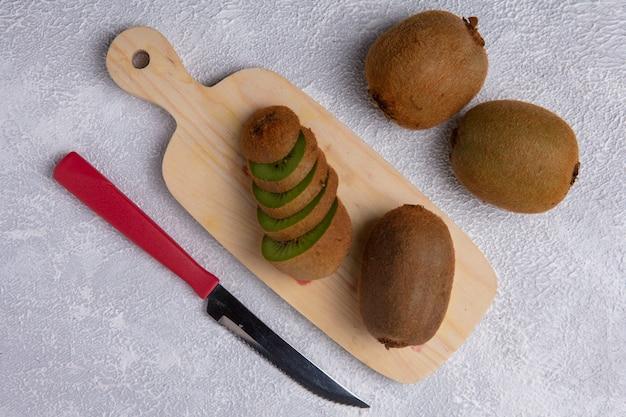 Bovenaanzicht kiwi op een snijplank met een mes op een witte achtergrond