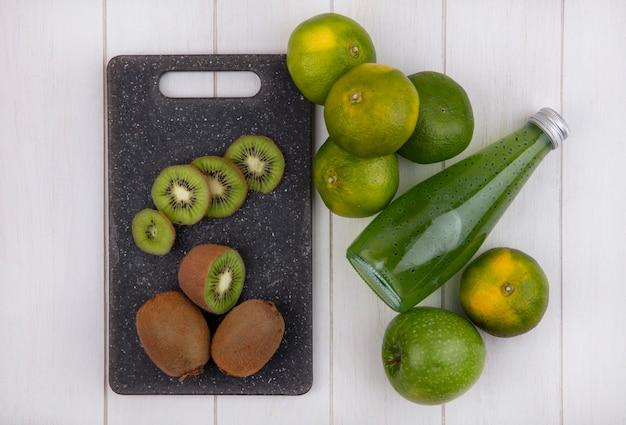 Bovenaanzicht kiwi op snijplank met mandarijnen appel en fles sap op witte muur