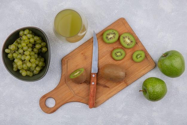Bovenaanzicht kiwi plakjes met een mes op een snijplank met groene appels en druiven in een kom met appelsap in een glas op een witte achtergrond