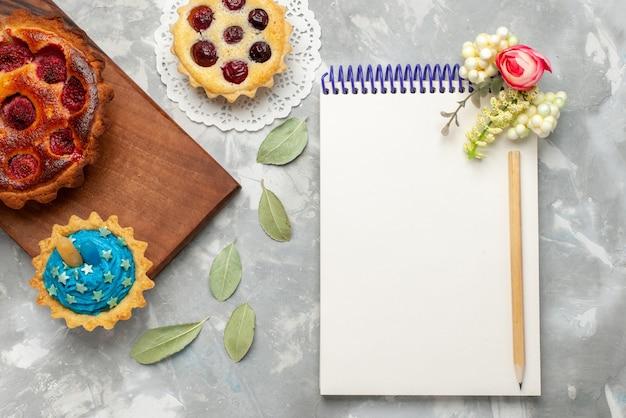 Bovenaanzicht kladblok en taarten op de lichte achtergrond cake taart fruit zoete suiker bakken