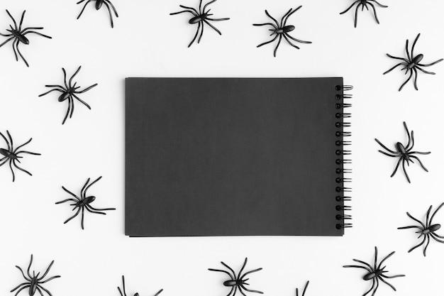 Bovenaanzicht kladblok omgeven door spinnen