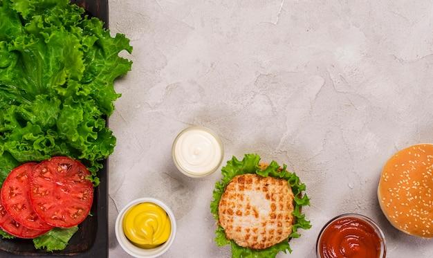 Bovenaanzicht klassieke hamburger met plakjes tomaat en dip