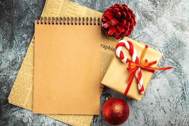 Bovenaanzicht klein cadeautje gebonden met rood lint notitieboekje op krant kerstboom speelgoed op grijs oppervlak