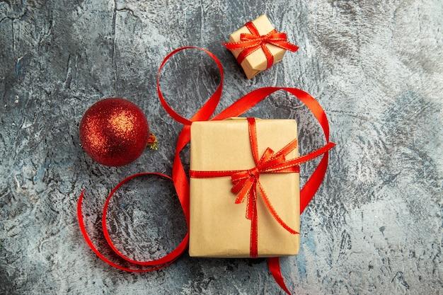 Bovenaanzicht klein cadeautje vastgebonden met rood lint kerstbal op donkere achtergrond