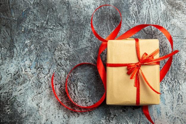 Bovenaanzicht klein cadeautje vastgebonden met rood lint op donker geïsoleerd oppervlak