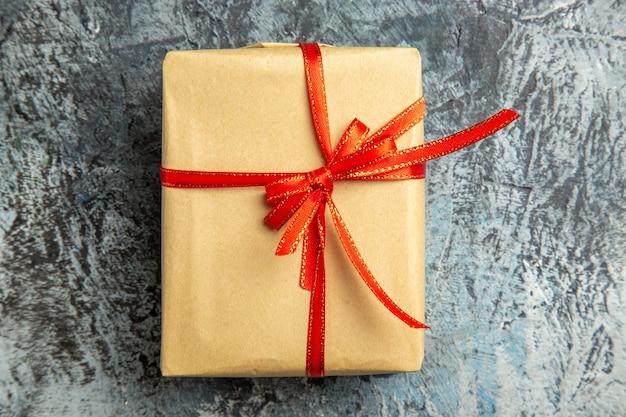 Bovenaanzicht klein cadeautje vastgebonden met rood lint op donkere achtergrond