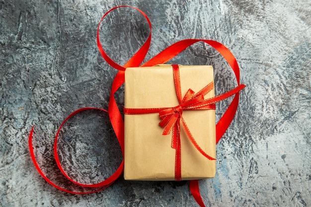 Bovenaanzicht klein cadeautje vastgebonden met rood lint op donkere geïsoleerde achtergrond