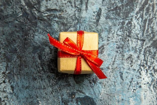 Bovenaanzicht klein cadeautje vastgebonden met rood lint op donkere ondergrond