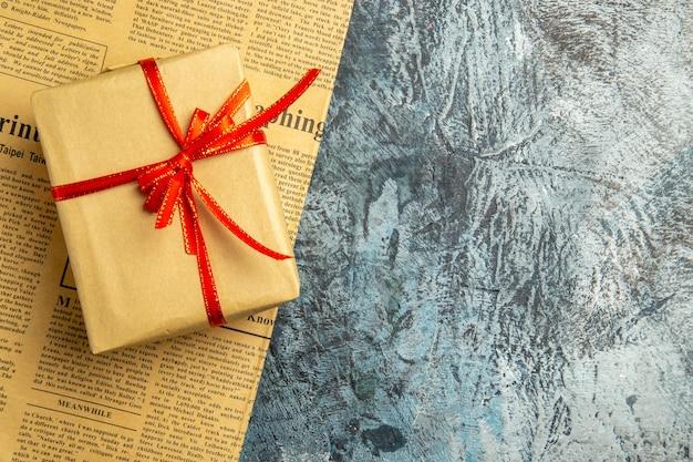 Bovenaanzicht klein cadeautje vastgebonden met rood lint op krant op donkere ondergrond